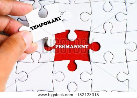 """""""PERMANENT"""" word on missing puzzle with a hand hold a piece of """"TEMPORARY"""" word puzzle want to complete it - business and finance concept poster"""