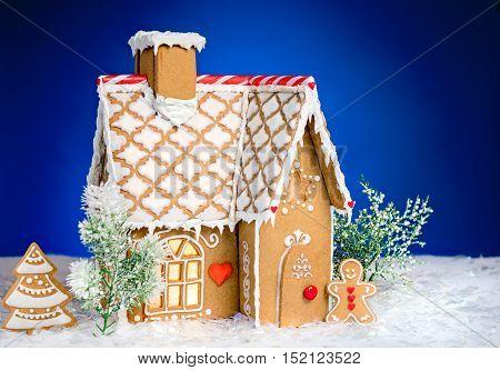 Homemade gingerbread house scene on blue background