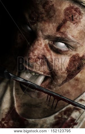 bloody zombie face with possessed white eyes licking knife