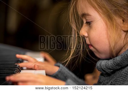 Little Girl Playing On The Keys Of The Piano