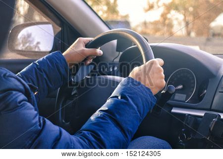 Man starts driving a car. Hand are on wheel. Sunny day