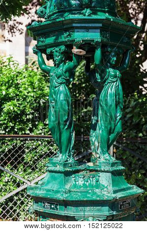 One of the drinking antique Wallace fountains with women group sculpture on Montmartre hill. Those fountains are recognized as one of the symbols of Paris