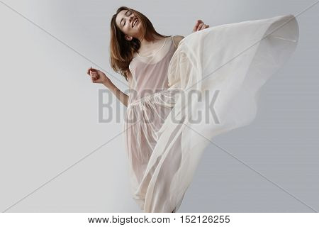 blonde woman wears transparent dress of balerina. blowed dress by wind