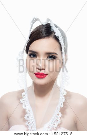 An attractive young woman with makeup on her face. Portrait of girl with dark hair on a white background. Beautiful bride with veil.