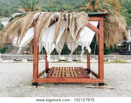 Beautiful wooden alcove for rest on beach with palm background