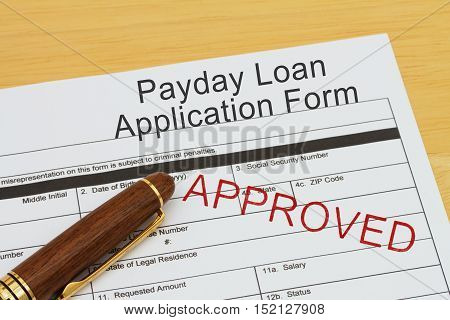 Applying for a Payday Loan Approved Payday loan application form with a pen on a desk with an approved stamp