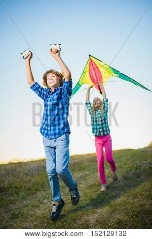 Group of happy and smiling kids playingin with kite outdoor.