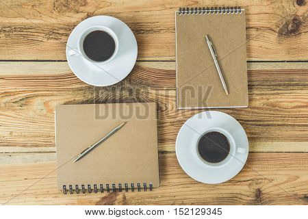 Everything you need for meeting. Top veiw of wooden table with two kraft notebooks, two pens and two cups of coffee on it
