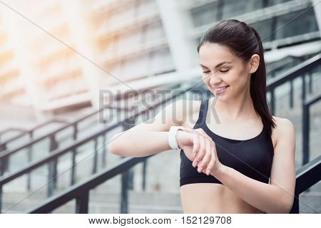 Time to work hard. Young pretty athletic girl wearing a sportswear and looking at her smart watch while waiting for training near the stadium.