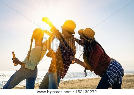 Cheering friends party and selfie holding beer bottle at sunset beach festival - Silhouette of happy teenagers having fun taking photo - University friendship concept in backlight scene with sun flare