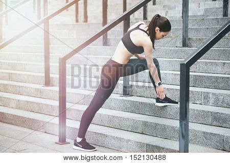 Keep yourself fit. Young slim pretty girl doing sport exercises and doing a lunge while standing on stadium stairs.