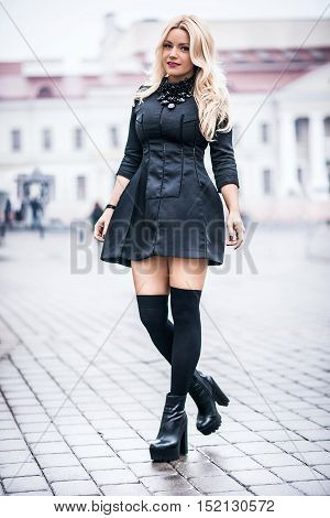 Young beautiful stylish classy girl wearing black dress, standing and posing in the city.