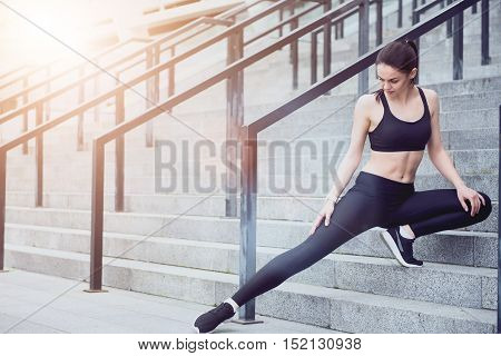 Get your legs ready. Beautiful young delighted girl warming up while stretching her legs and preparing for outdoors training.