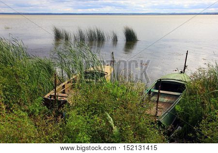 two old metal boats at the shore of a large lake Nero in summer and the reeds in the water