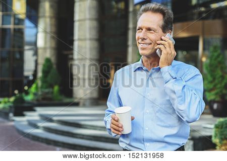 Connected to modern life. Adult handsome businessman standing outside with smartphone while drinking coffee