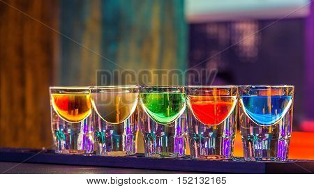 Colorful shot drinks in bar in night