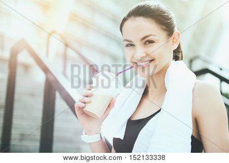 Happy relaxation. Beautiful sporty athletic woman smiling and relaxing after working out in an urban environment.