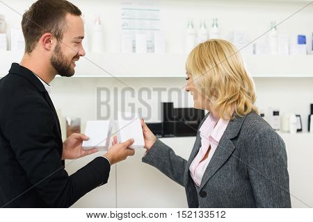 Polite male shop assistant is showing cream to senior woman. They are standing and smiling