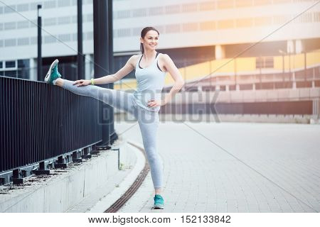Cheerful exercise. Athletic young beautiful woman smiling and stretching while exercising in urban surroundings.