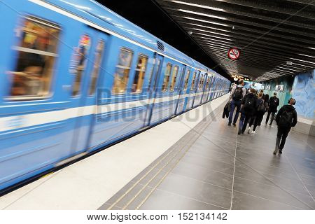 Stockholm, Sweden - May 7, 2015: Interor of the subway station Stadion in the Stockholm Metro. People walking on the plattform to the exit while a blue train leaving the station heading for Morby Centrum.