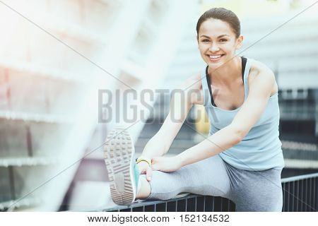 Cheerful exercise. Beautiful slim sporty woman exercising outdoors while stretching and smiling.