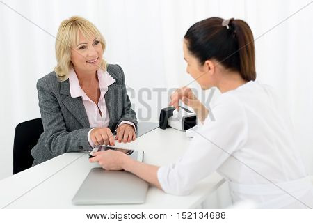 Professional cosmetologist is advising cosmetology procedure to senior woman. She is showing tablet to her. Mature lady is sitting and smiling