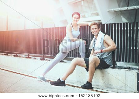 Active lifestyle together. Beautiful slim woman and a fit man smiling and resting together after training outdoors.