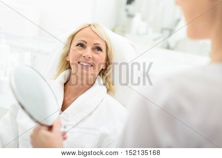 Happy senior woman is satisfied with her skin after procedure. She is sitting at beautician office and smiling. Doctor is holding mirror
