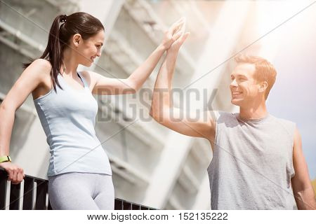 Greetings after exercises. Beautiful slim woman and a fit man smiling and high fiving each other after training outdoors.