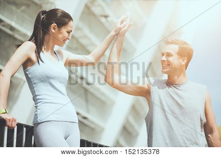 Fitness high five. Beautiful cheerful woman and a handsome man smiling and high fiving each other after working out in an urban setting.