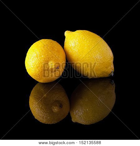 Two lemon with water drops isolated on a black glossy background with realistic reflection