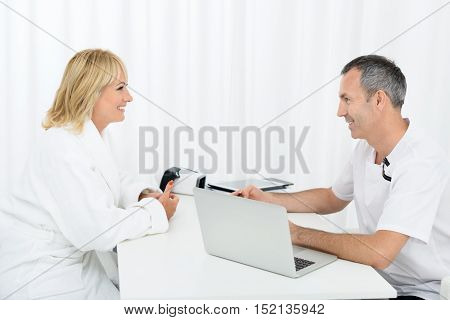 Professional male beautician is consulting mature woman at clinic. They are sitting at desk and smiling