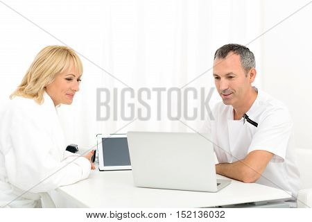 Experienced male beautician is explaining spa procedure to senior woman. They are looking at laptop and smiling
