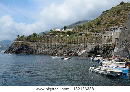 Manarola Italy - September 4 2016: Boats in small port in Manarola city in Liguria Italy. One of five Cinque Terre cities (unesco world heritage). Unidentified people visible.