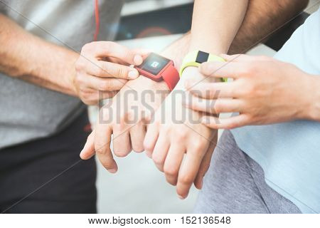 Sharing exercise performance. Active and sporty couple looking at their smartwatches and sharing data after working out outdoors