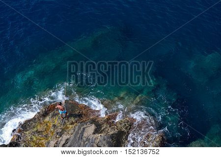 Manarola Italy - September 4 2016: Unidetified angler catching fish on rocky shore in Manarola in Liguria Italy. One of five Cinque Terre cities (unesco world heritage)
