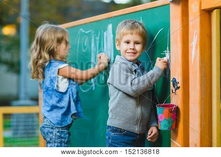 Cute children drawing with chalk on blackboard outdoor.