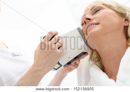 Relaxed mature woman is receiving facial skin care treatment by massager. She is sitting at wellness center and smiling
