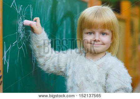 Cute child drawing with chalk on blackboard outdoor.
