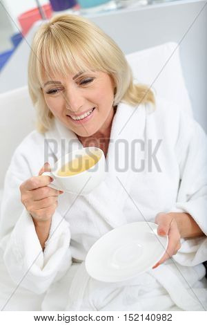 Enjoying harmony at home. Serene middle-aged woman is relaxing with hot tea and smiling. She is wearing white bathrobe