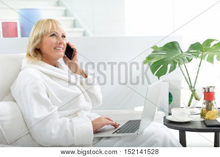 Mature woman is relaxing in bathrobe at home. She is talking on mobile phone and smiling. Woman is sitting and holding laptop
