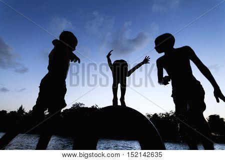 Silhouette Of Three Boys Having Fun By Jumping Into A River In Brazil - Catu River, Sibauma, Tibau D