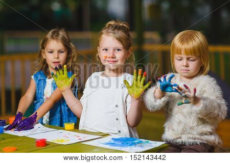 Children having fun painting with finger paint.