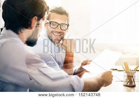 New solutions. Smiling bearded businessman wearing glasses is giving new contract to his business partner on white light background.