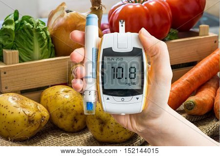 Hand Holds Glucometer For Measuring Glucose Level. Vegetables In