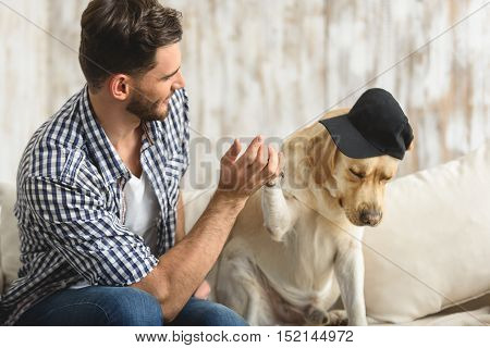 high five, puppy giving high five to a handsome guy on a couch