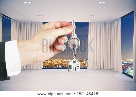 Close up of hand holding key with house chain in modern interior with night city view. Property concept