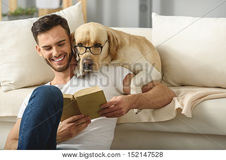 clever dog in glasses reading book with a bearded man