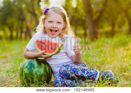 cute little girl width watermelon sitting on grass outdoor.