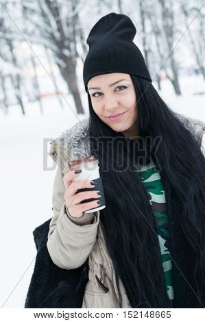 Closeup outdoor portrait of beautiful young Caucasian woman, holding a cup of takeaway coffee, standing in park on snowy winter day, smiling, wearing jacket, black beanie hat and black scarf